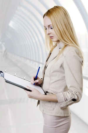 sexual blonde business woman in elegant suit writing a document in a folder in light modern hall in office building photo