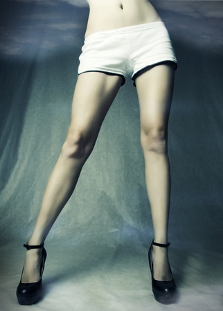 Long sexy slim female legs in black shoes and shorts in studio. Stock Photo - 9276871