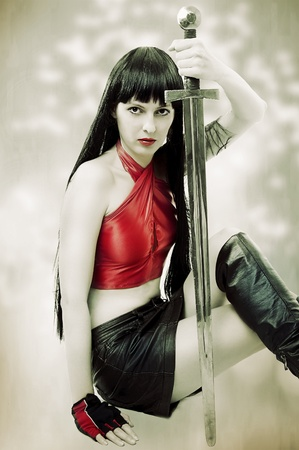 Fashion portrait of young pretty brunette woman with long hair. She holding a sword photo