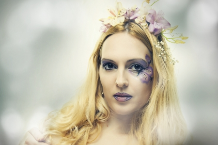 Fashion portrait of young beautiful woman with flowers in hair closeup. Fairy photo