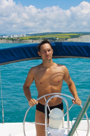 Young sexy skipper driving sailboat  Captain of the yacht at sea or ocean photo