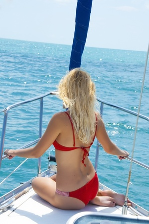 Attractive sexual woman sitting on the front of large and luxurious sailboat sailing through the tropics Stock Photo - 10017512