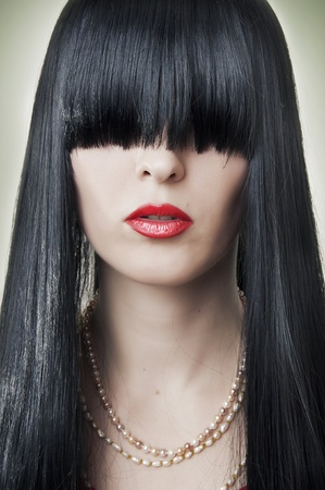 Portrait of female face with creative hairstyle - long black hair. Fashion makeup - classic red lips. Stock Photo