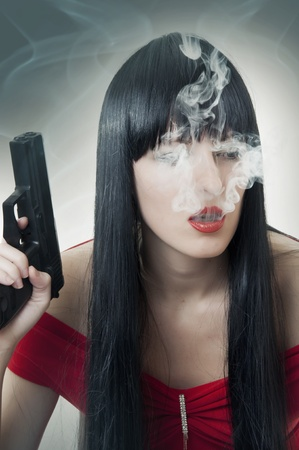 Fashion portrait of woman with handgun and cigarette photo