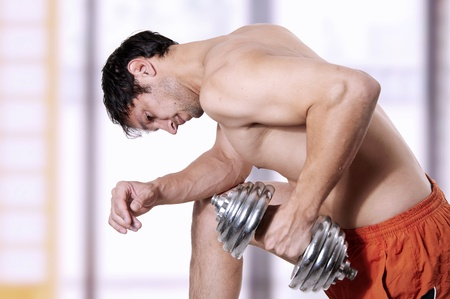 Powerful young adult muscular man training (working out) - lifting weights photo
