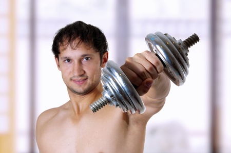 get out: Muscular man training with dumbbell. Focus on dumbbell only
