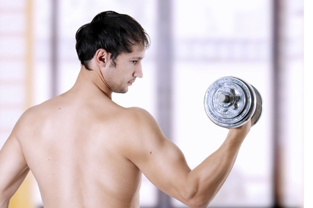get a workout: Powerful young adult muscular man training (working out) - lifting weights