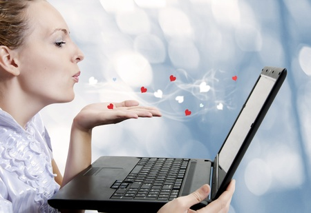 kiss love: Concept - young attractive woman love laptop computer or internet boyfriend. She sending Air kiss to screen