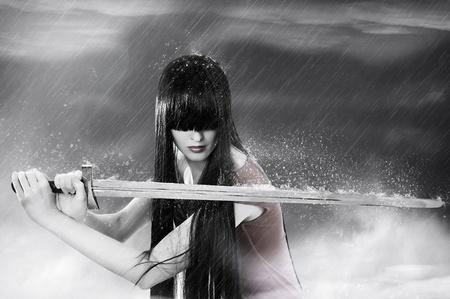 Retrato de fantasía de moda de caza bastante Morena joven con espada en niebla