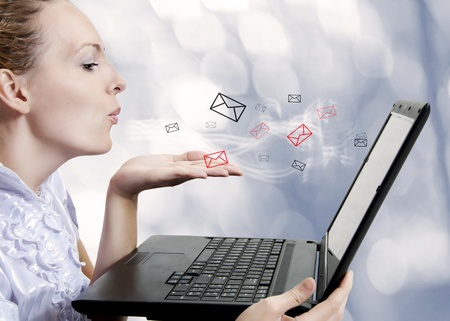 Concept - young attractive woman with laptop computer sending emails on forum, chat or blog. Blogger Stock Photo