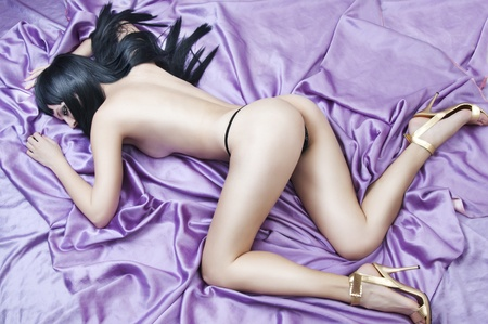 Sexual nude woman lying on violet silk bed after sex Stock Photo - 10171069