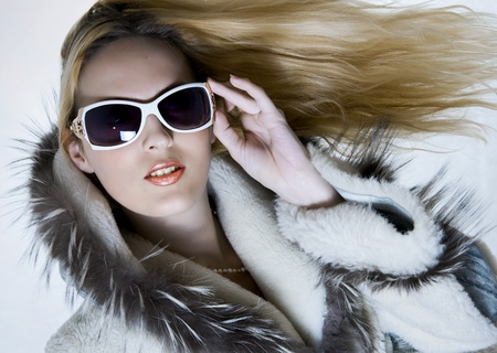 Fashion portrait of beautiful woman in fur coat and designers sunglasses with long flying hair photo
