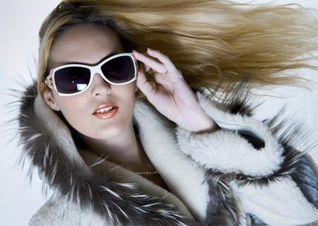 bontjas: Mode portret van mooie vrouw in bont jas en ontwerpers zonnebril met lange haren vliegen