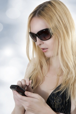 touch screen phone: Portrait of cute blonde woman in sunglasses with touch screen sellphone