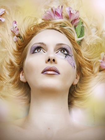 Fashion blur portrait of beauty woman face with art floral make up and flowers in hair Stock Photo - 10262774