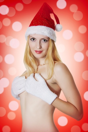 Portrait of young female model in red santas cap smiling and looking in a shot. photo