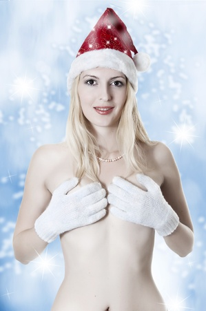 Portrait of beautiful sexy woman in santa hat on blue background with snowflackes photo