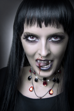 Fashion portrait of woman vampire or demon with blood  photo