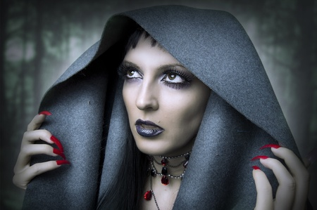 Fashion portrait of young beauty woman - witch in dark forest. Makeup and style for halloween photo
