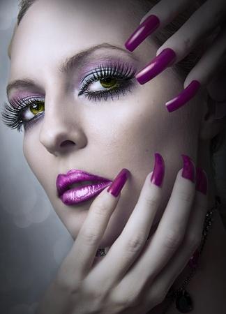 패션 밝은 저녁의 아름 다운 여자의 초상화 메이크업과 손톱의 아름다움 보라색 매니큐어. 여성 얼굴의 근접 촬영