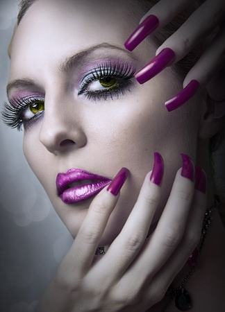 Portrait of beautiful woman of fashion bright evening make up and beauty purple manicure of fingernails . Female face closeup