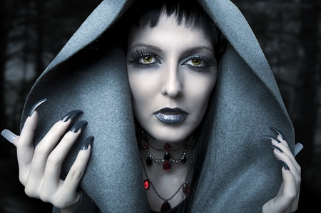 Halloween. Fashion portrait of witch or night vampire woman. Dark gothic makeup photo