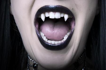 口: 吸血鬼の女の悲鳴の長い白い牙クローズ アップで口を開いた。ハロウィーンのためのメイクアップします。
