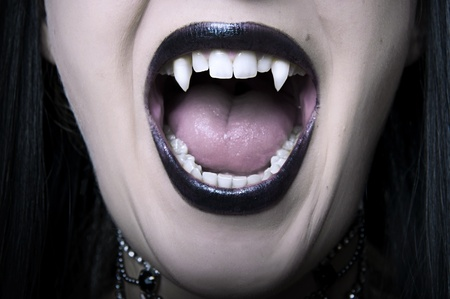 fangs: Opened mouth with long white fangs closeup of screaming vampire woman. Make up for halloween