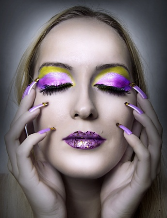 Portrait of beautiful woman with fashion bright christmas make up and beauty purple and golden manicure of fingernails . Female face closeup