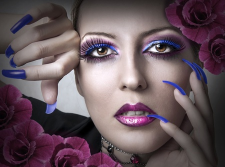 Portrait of beauty woman with fashion bright evening makeup and beauty purple manicure of fingernails and flowers