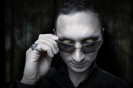 satanas: Estilo de Halloween. Retrato de noche estilo masculino de vampiro o demonio conforman sobre fondo oscuro