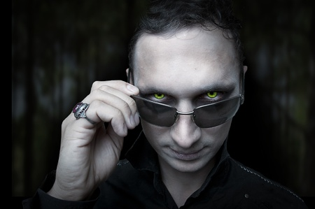 mach 1: Portrait of Night male vampire or demon style make up on dark background Stock Photo