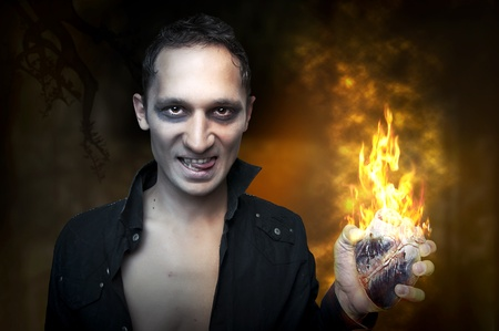 vampire: Portrait of handsome man - night vampire, demon or zombie, holding in hand heart burn in fire Stock Photo