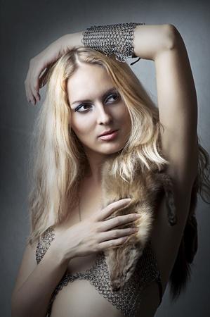 chain armour: Fashion studio portrait of young adult beautiful sexy model in chain armour bikini Stock Photo