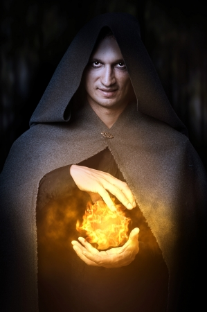 Halloween concept. Powerful Male witch or wizard with fireball in hands. Ball from fire burns photo