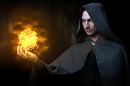 Halloween concept. Krachtige Man heks of tovenaar met een vuurbal in handen. Bal van vuur brandt Stockfoto