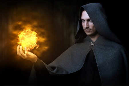 Halloween concept. Powerful Male witch or wizard with fireball in hands. Ball from fire burns Stock Photo