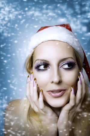 Christmas bright make-up and long nails manicure concept. Portrait of young woman model at santa hat, face closeup photo