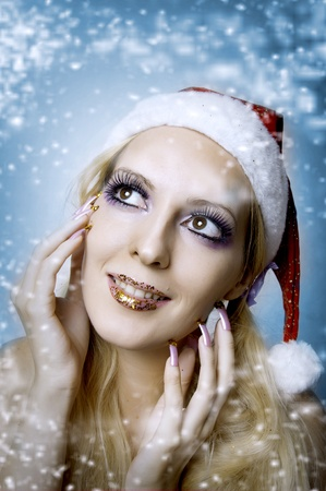 Christmas bright make-up and long nails manicure concept. Portrait of young woman model at santa hat, face closeup Stock Photo