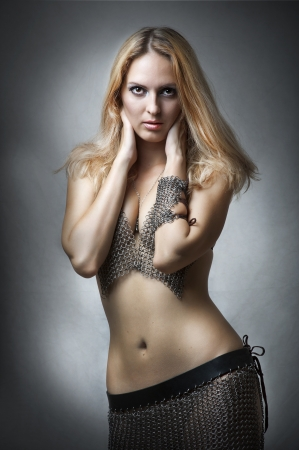 waist up: Fashion studio portrait of young adult beautiful sexy model in chain armour bikini and skirt
