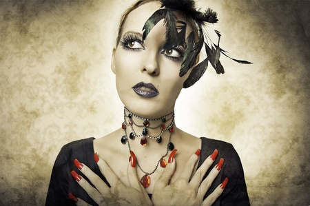 Glamour portrait in retro style of beauty young woman in black dress with long red finger nails, necklace and dark make up. Closeup sexy model face. Costume for halloween photo
