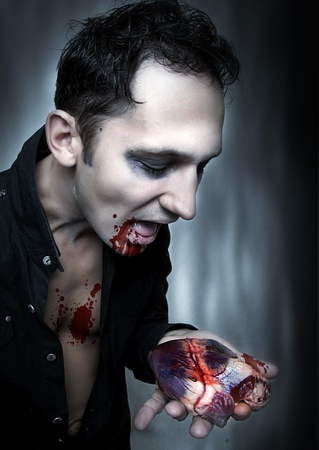 demoniacal: Halloween. Vampire eat heart. Dark portrait of witch or zombie and blood