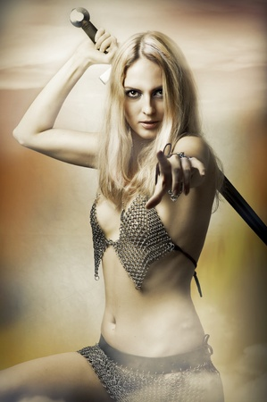 Fantasy portrait of medieval woman fighter with sword in sexy armour pointing at camera. Joan of Arc Stock Photo