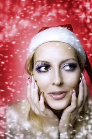 shoked: Christmas bright make-up and long nails manicure concept. Portrait of young woman model at santa hat, face closeup Stock Photo