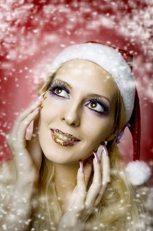 uñas largas: Navidad brillante maquillaje y manicura concepto durante mucho tiempo las uñas. Retrato de modelo de mujer joven en el sombrero de santa, primer de la cara Foto de archivo