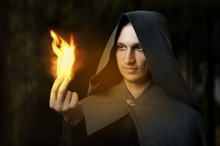 Halloween concept. Powerful Male witch or wizard with firel in hands. Ball from fire burns. Fantasy magic