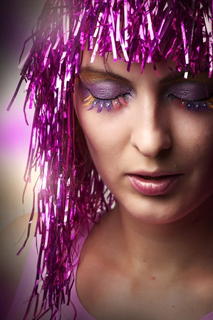 Bright glamour make-up for party or celebration. Fashion  portrait of female model face closeup. carnival wearing glossy pink wig photo