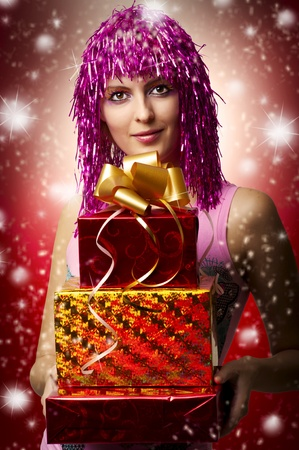 Glamour portrait of christmas happy woman model who holding three red, yellow boxes with gifts or christmas presents in hands. christmas presents photo