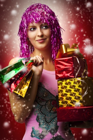 Glamour portrait of christmas happy woman model who holding three red, yellow boxes with gifts or christmas presents in hands. christmas presents and shoppig bags photo