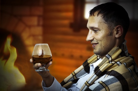siting: Taster. Young adult Man in tartan plaid holding in hand a glass of classy extra old brandy or cognac. He is inside home room siting about fireplace
